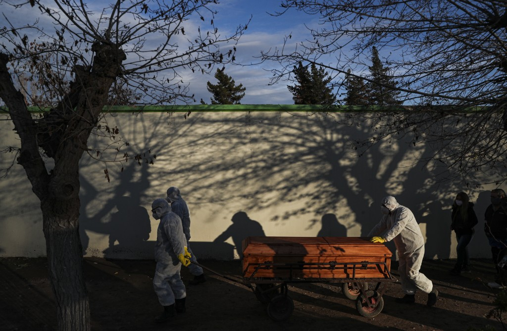 A coffin that contains the remains of Marco Antonio Marquez who died of complications related to COVID-19 is guided by workers through the Bajos de Me...