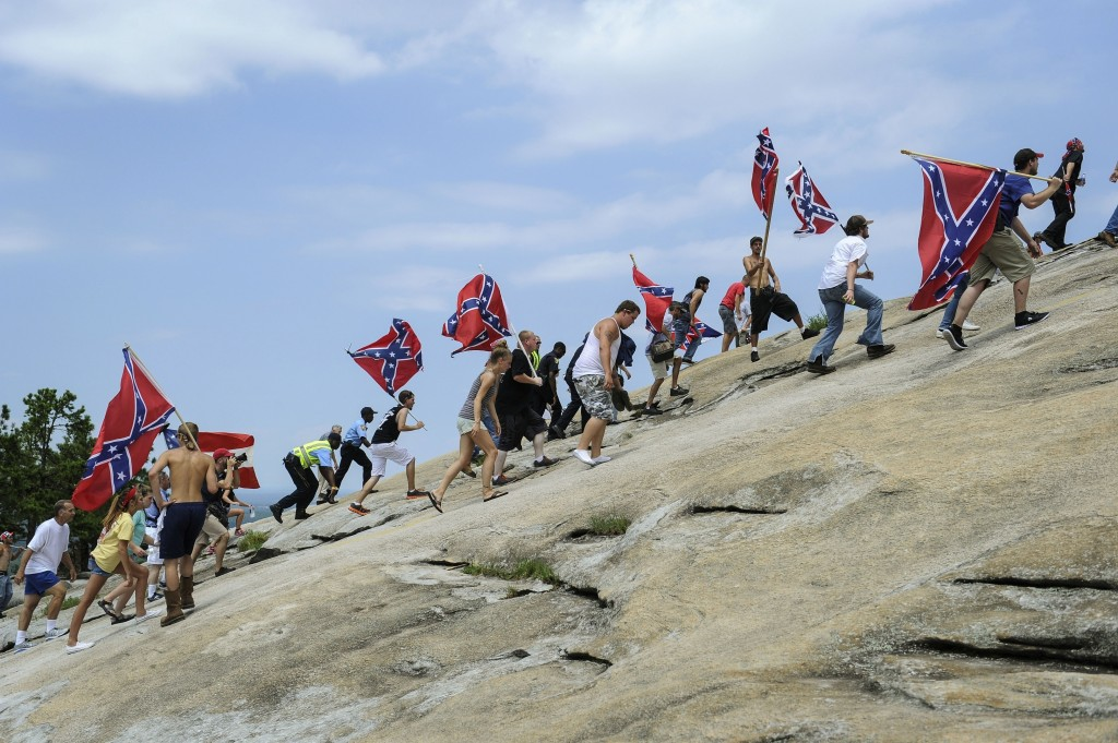 FILE - In this Aug. 1, 2015 file photo, Confederate flag supporters climb Stone Mountain to protest of what they believe is an attack on their Souther...