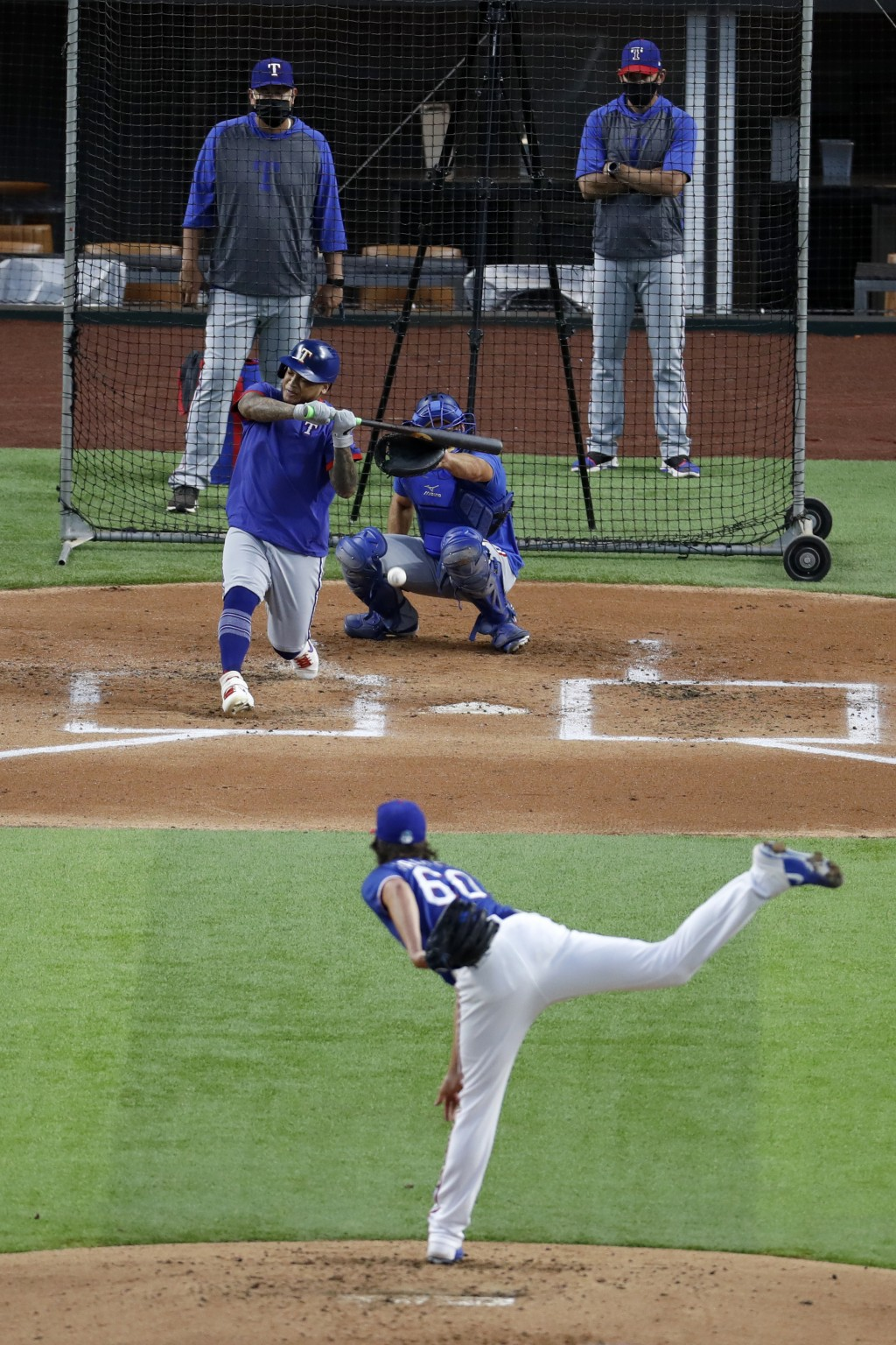 Texas Rangers' Luke Farrell throws to Willie Calhoun as catcher Jeff Mathis, pitching coach Julio Rangel, left rear and manager Chris Woodward, right ...