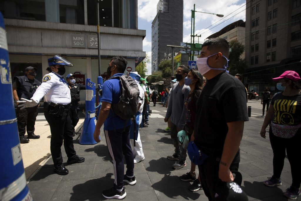 A Mexican police officer gives social-distancing and precautionary COVID-19 related guidelines to tourists in the historic center of Mexico City, Frid...