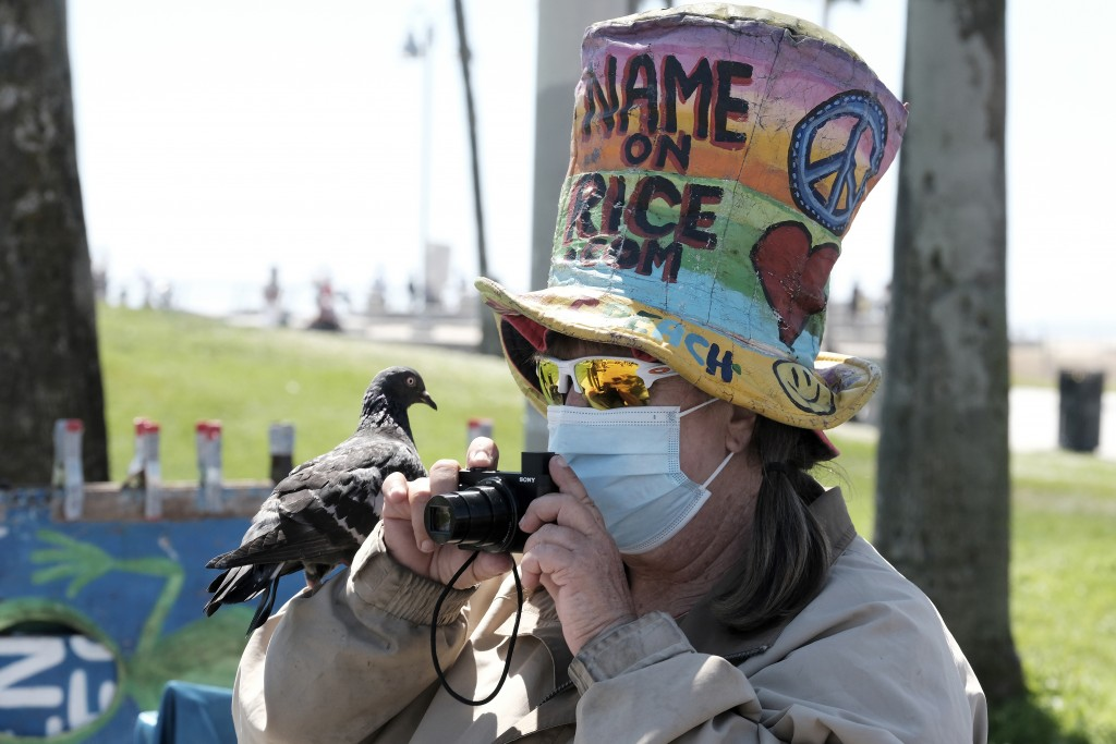Vendor Vivianne Robinson, wearing a mask to protect from the coronavirus, takes a photo with a pigeon perched on her hand along the Venice Beach stran...