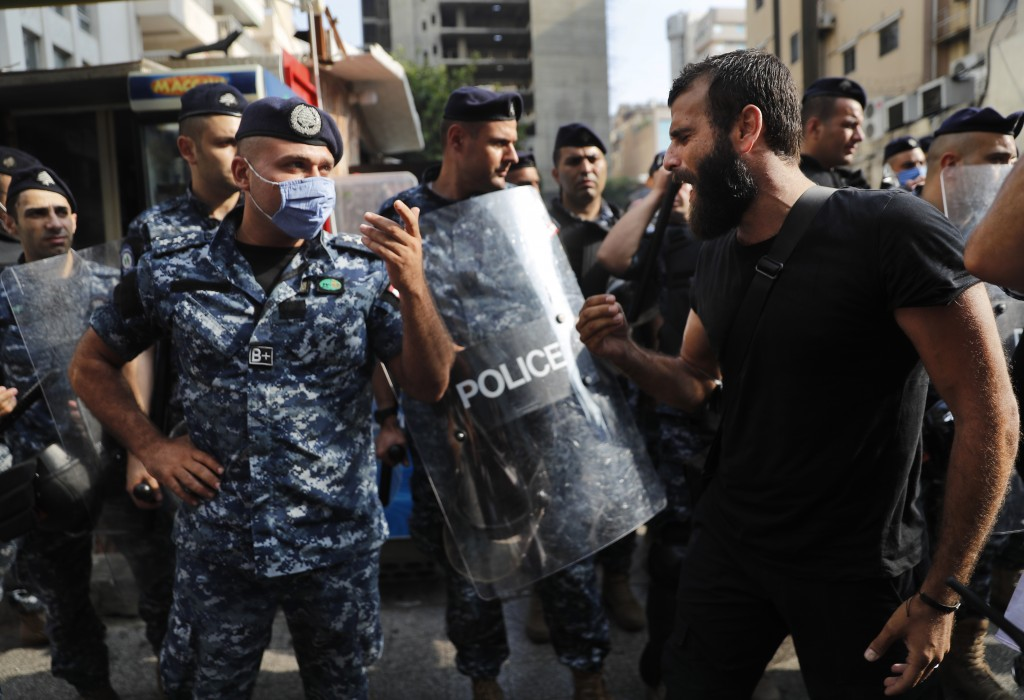 An anti-government protester shouts at riot police, near the scene where a Lebanese man killed himself on Beirut's commercial Hamra Street, apparently...