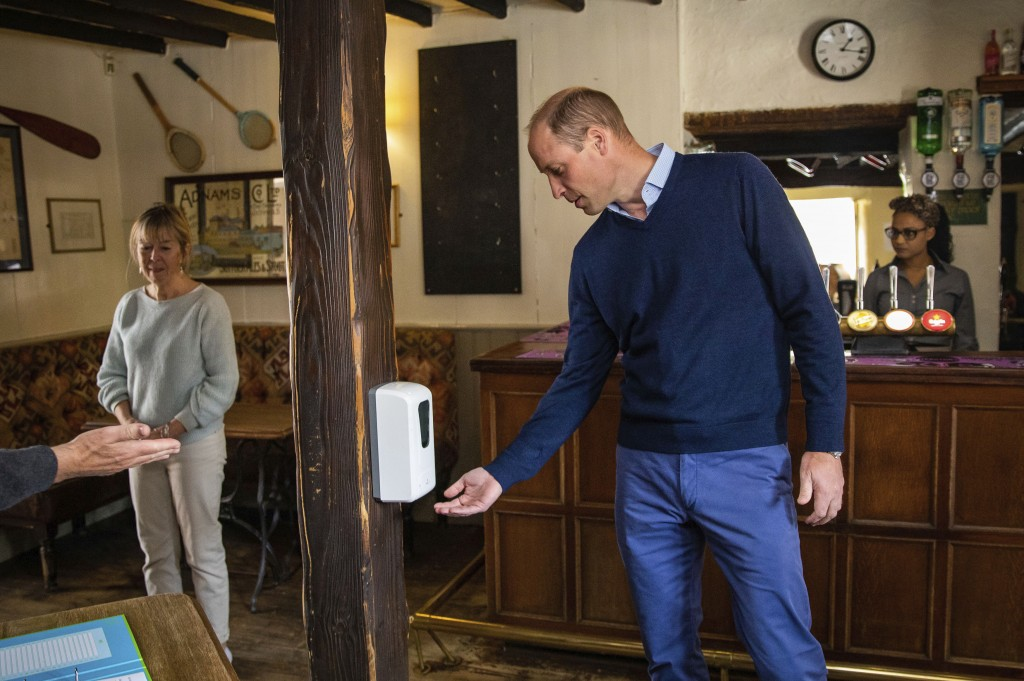 Britain's Prince William uses hand sanitiser as he enters The Rose and Crown pub in Snettisham, England, Friday July 3, 2020.   English pubs are among...