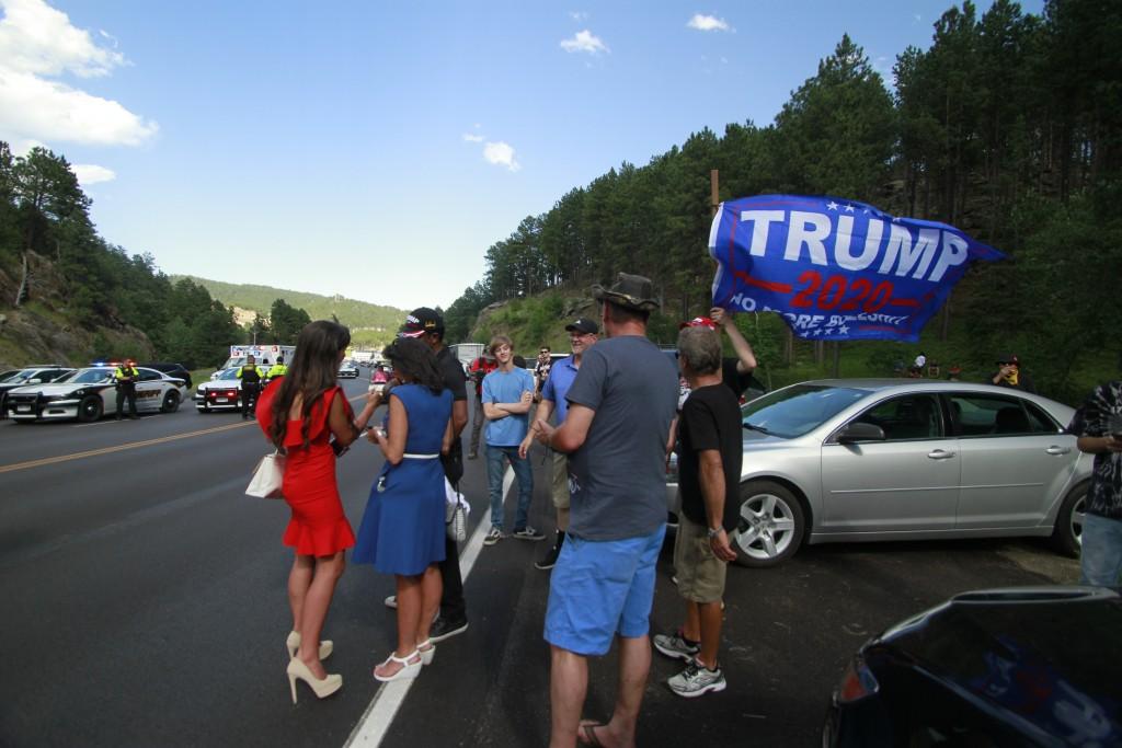 Trump supporters, some who were blocked from reaching Mount Rushmore by a blockade set up by Native American protesters, gather near where protesters ...