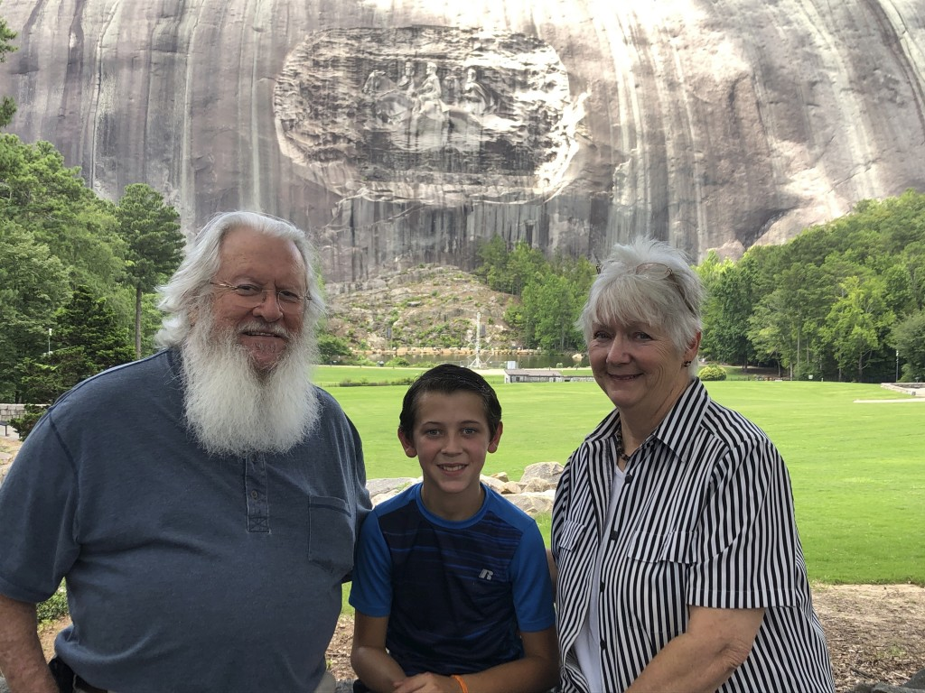Paula and Michael Smith pose for a photo with their 10-year-old grandson, Evan, in front of a giant carving of Confederate figures during a visit to S...