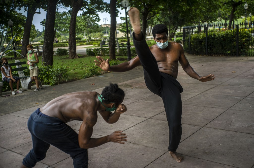Wearing protective face masks as a precaution against the spread of the new coronavirus, Victor Rafael Torres, left, and Eiver Carbonell, train in cap...