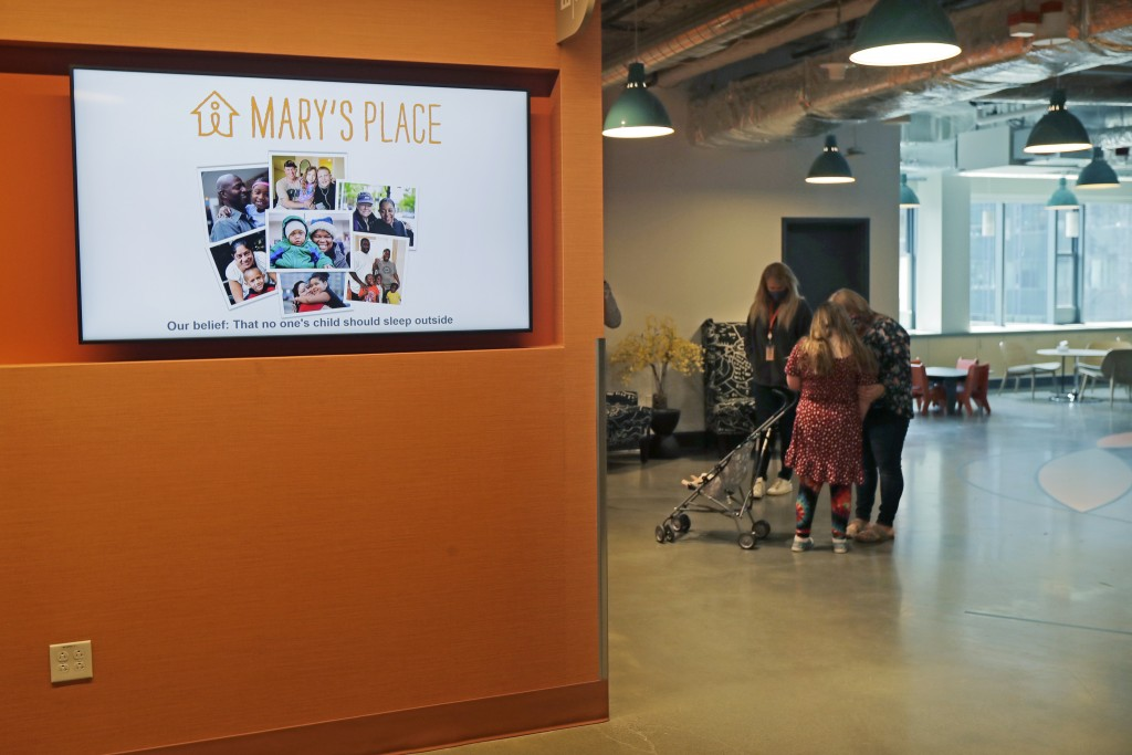 A video display shows photos and the logo for Mary's Place, a family homeless shelter located inside an Amazon corporate building on the tech giant's ...