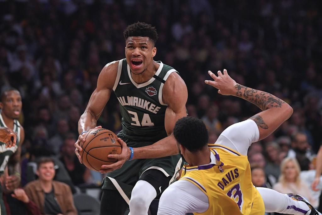 FILE - In this March 6, 2020, file photo, Milwaukee Bucks forward Giannis Antetokounmpo knocks down Los Angeles Lakers forward Anthony Davis as he dri...