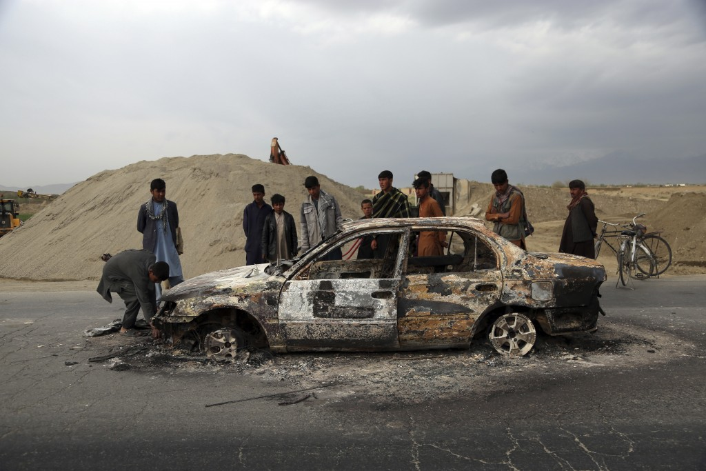 FILE - In this April 9, 2019, file photo, Afghans watch a civilian vehicle burnt after being shot by U.S. forces following an attack near the Bagram A...