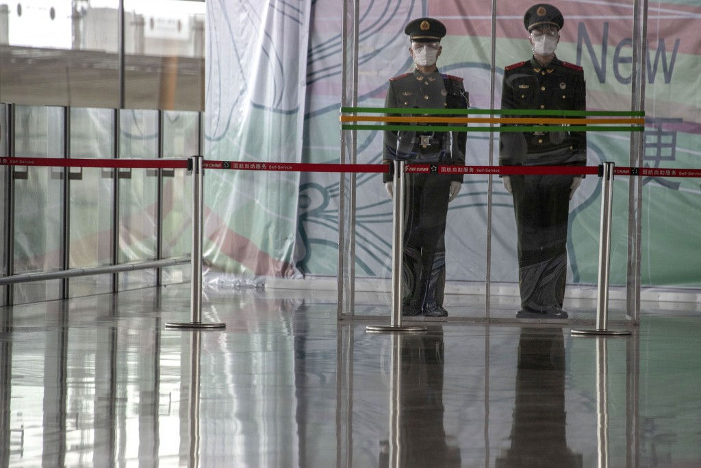 FILE - In this March 12, 2020, file photo, Chinese paramilitary policemen stand on duty behind a barrier at the Capital International Airport terminal...