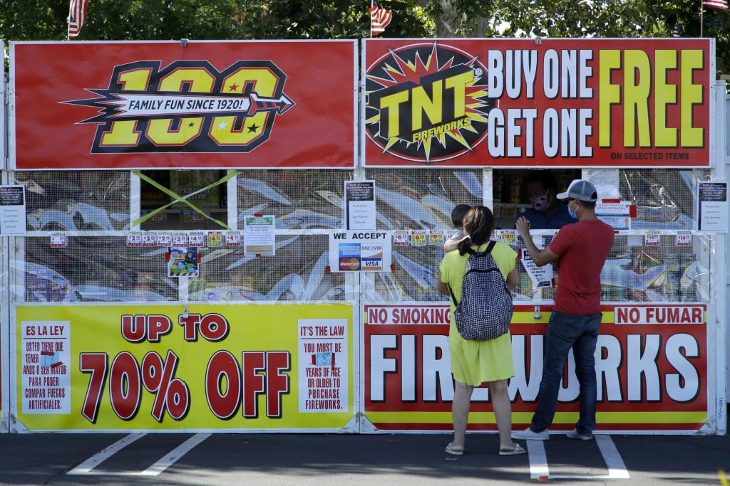 People purchase fireworks on Thursday, July 2, 2020, in Dublin, Calif. For many Americans, the Fourth of July won't be about big festivities but setti...