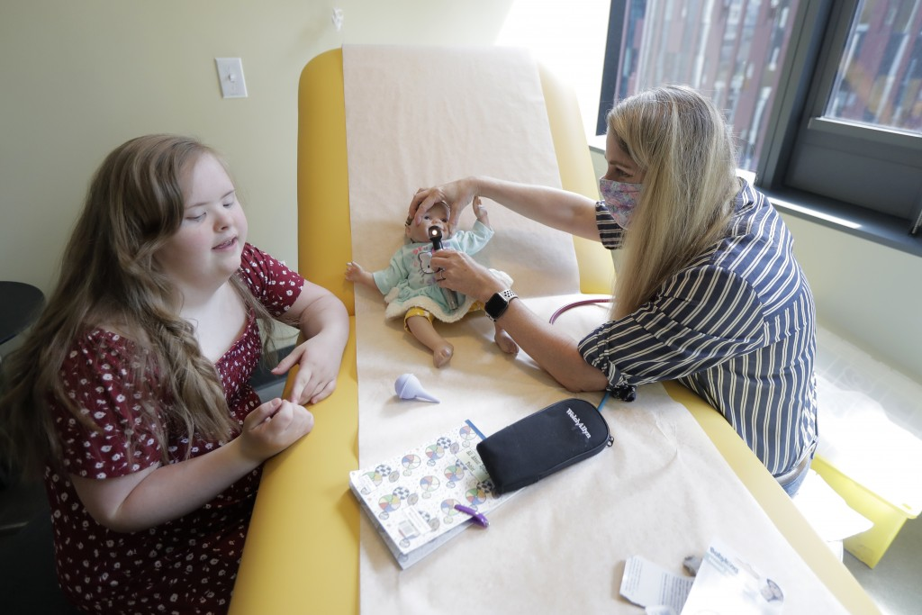 Emilyanne Wade, 12, left, looks on as Tricia Nora, a pediatric nurse practitioner, examines Sophia, Wade's baby doll, Wednesday, June 17, 2020, in a m...