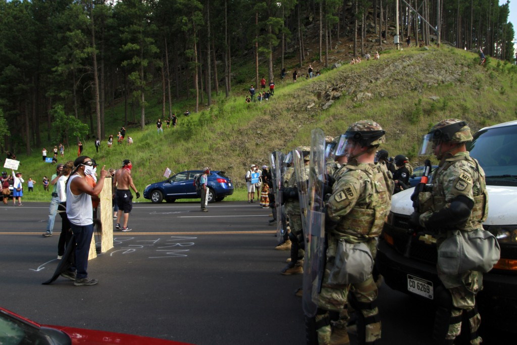 Native American protesters confront a line of law enforcement officers in Keystone, S.D., on the road leading to Mount Rushmore ahead of President Don...