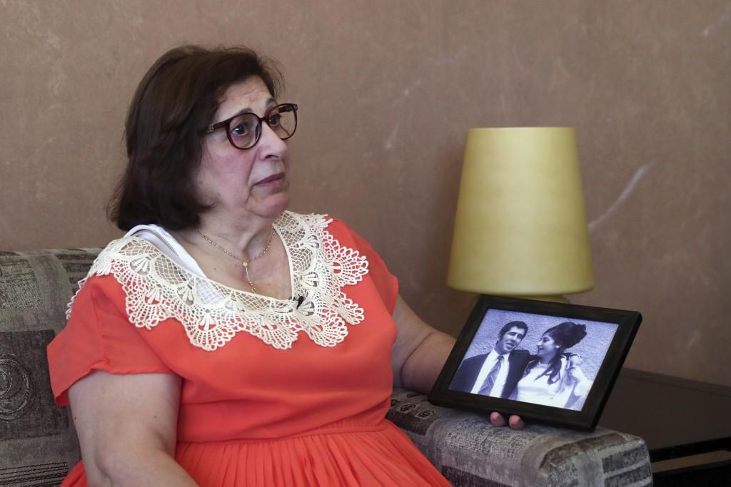 Laure Ghosn, whose husband Charbel Zogheib has been missing for the past 37 years, speaks as she holds their wedding portrait during an interview at h...