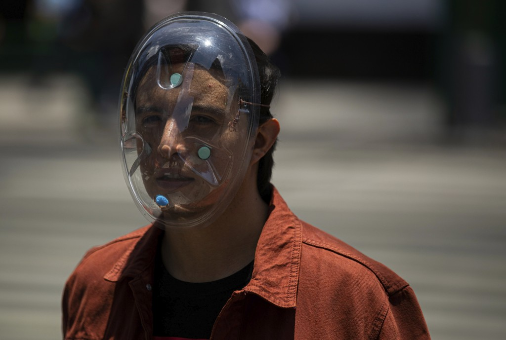 A pedestrian wears a makeshift face mask as a precaution against the spread of COVID-19, in downtown Mexico City, Friday, July 3, 2020. Limited reopen...