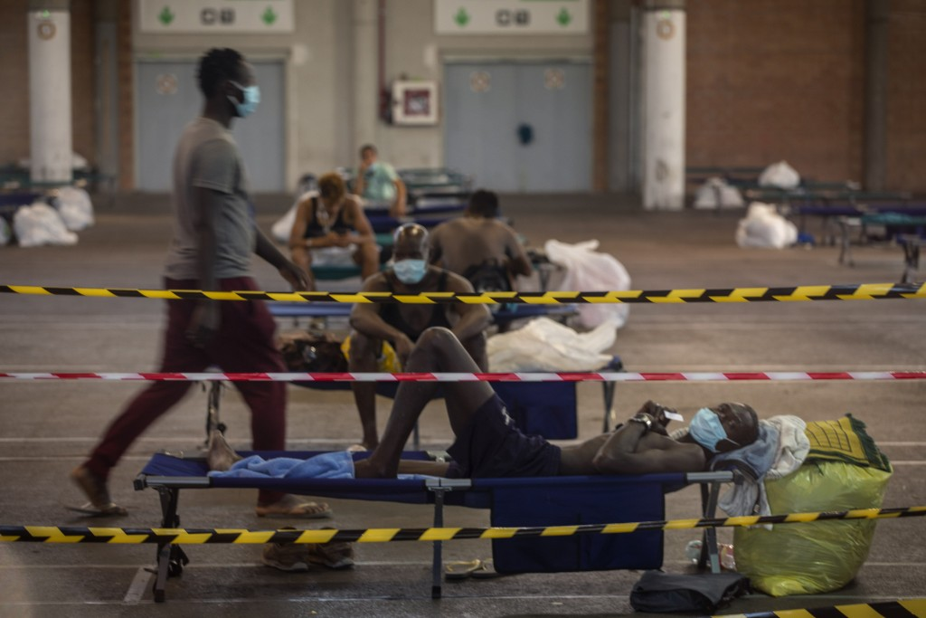 Migrants rest inside an exhibition center turned into temporary seasonal workers' shelter in Lleida, Spain, Thursday, July 2, 2020. Authorities in nor...