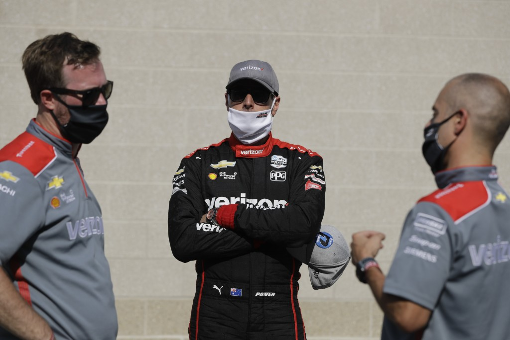Race driver driver Will Power, middle, of Australia, talks with his crew after winning the pole for the IndyCar auto race at Indianapolis Motor Speedw...