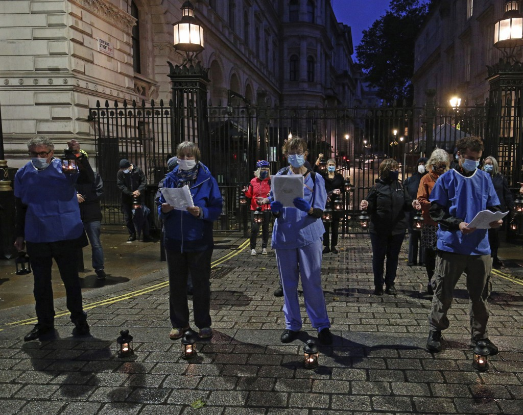 NHS staff and campaigners stand outside Downing Street, in London, Friday, July 3, 2020, reading out the names of NHS staff who have died from the cor...