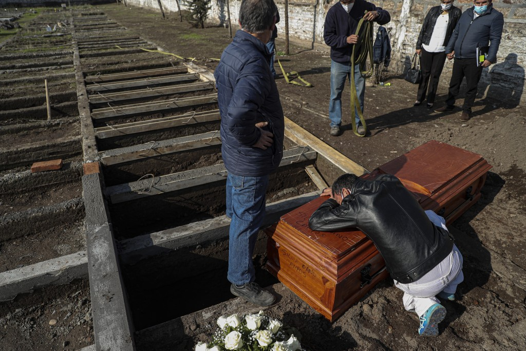 Peruvian migrant Jose Collantes grieves as he cries on the coffin that contains the remains of his wife Silvia Cano, who died due to COVID-19 complica...