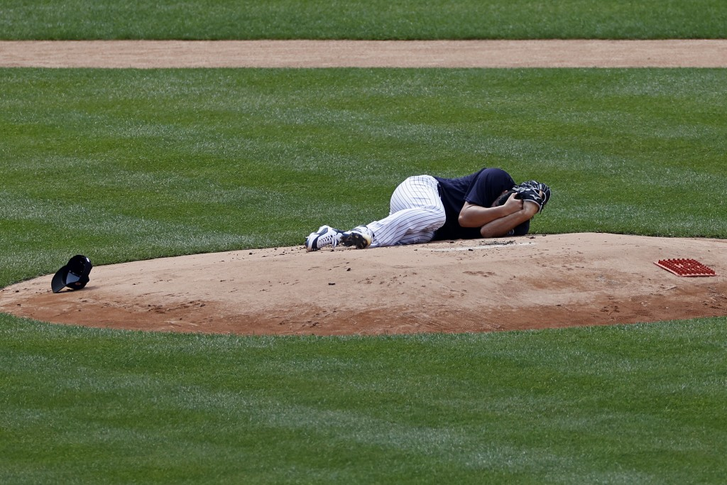 New York Yankees pitcher Masahiro Tanaka lies on the field after being hit by a ball off the bat of Yankees Giancarlo Stanton during a baseball a work...