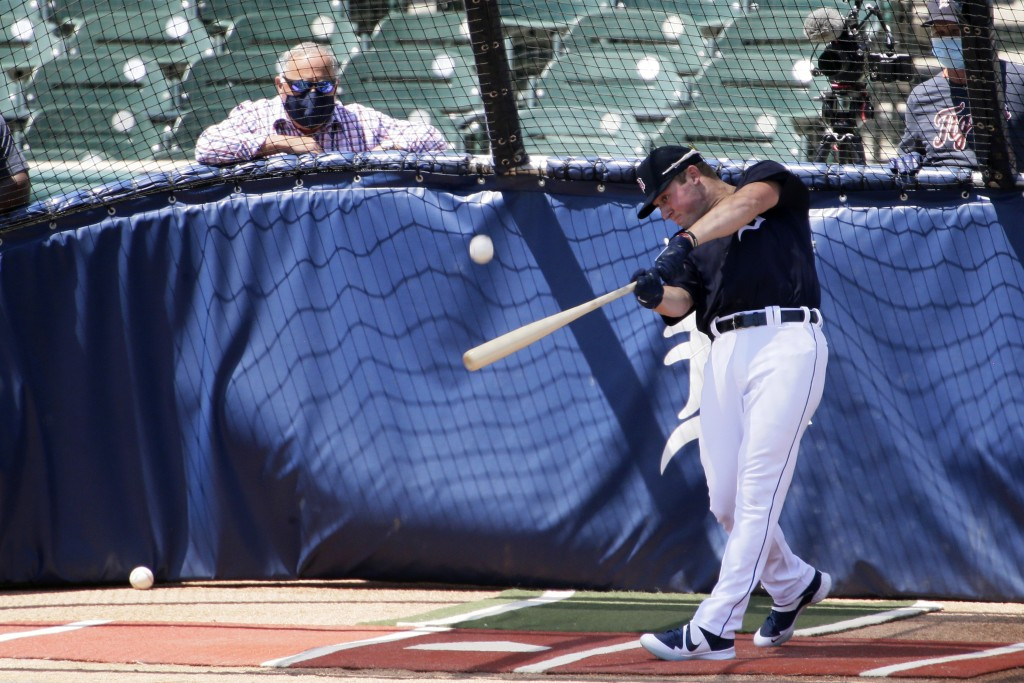 Detroit Tigers' Spencer Torkelson hits in the batting cage as Tigers general manager Al Avila, left, watches during baseball training camp at Comerica...