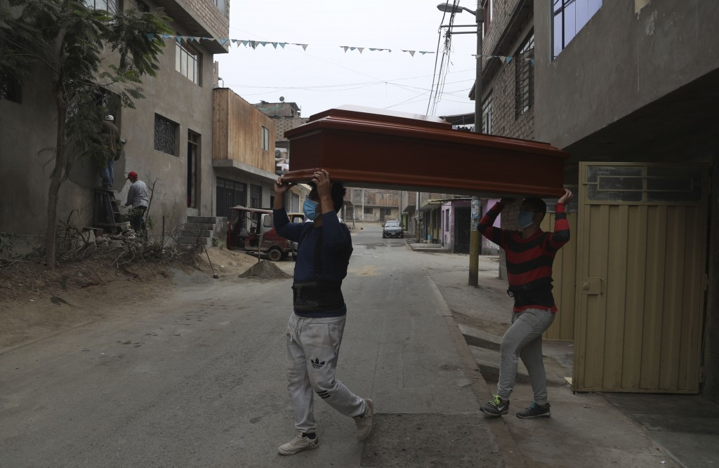 Workers carry a newly-made coffin at a factory in the Juan de Lurigancho neighborhood of Lima, Peru, Saturday, July 4, 2020.  Peru has reported one of...