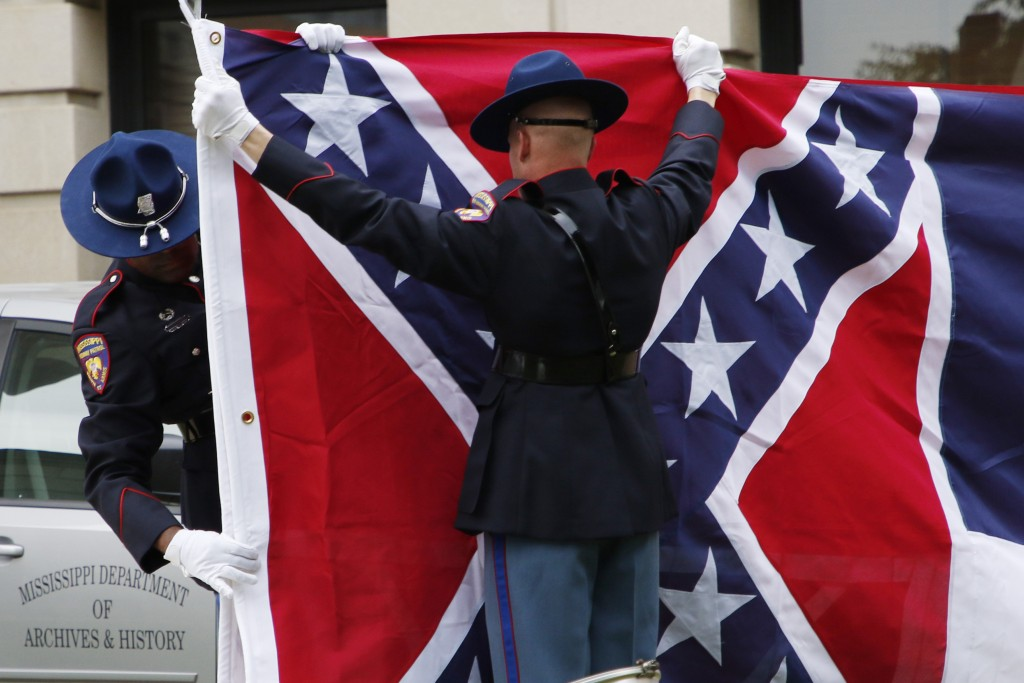 A Mississippi Highway Safety Patrol honor guard folds the retired Mississippi state flag after it was raised over the Capitol grounds one final time i...
