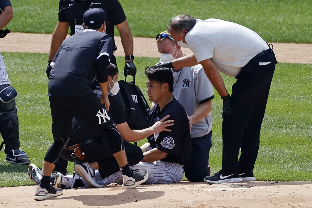 New York Yankees pitcher Masahiro Tanaka is tended to by team medical personnel after being hit by a ball off the bat of Yankees Giancarlo Stanton dur...