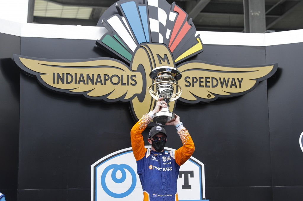 Race driver Scott Dixon, of New Zealand, celebrates with the trophy after winning the IndyCar auto race at Indianapolis Motor Speedway in Indianapolis...