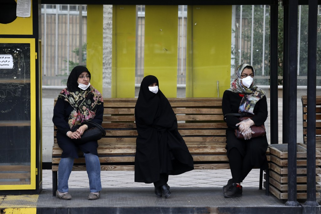 People wearing protective face masks to help prevent the spread of the coronavirus sit at a bus stop in the city of Zanjan, some 330 kilometers (205 m...