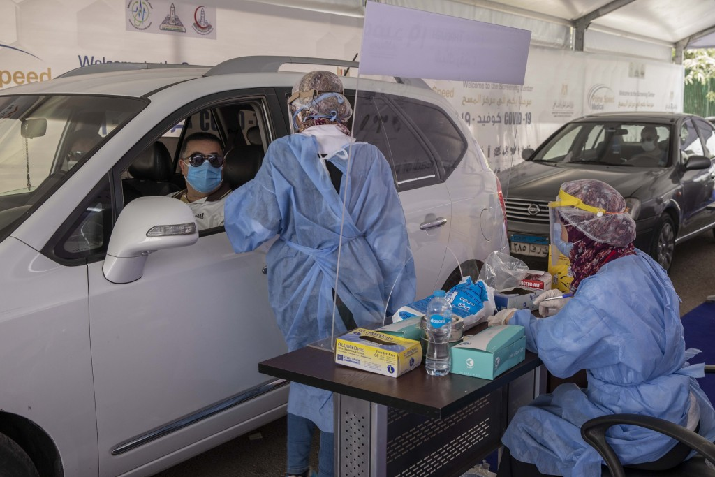 FILE - In this June 17, 2020 file photo, a health worker wearing protective gear prepares to take swab samples from people queuing in their cars to te...