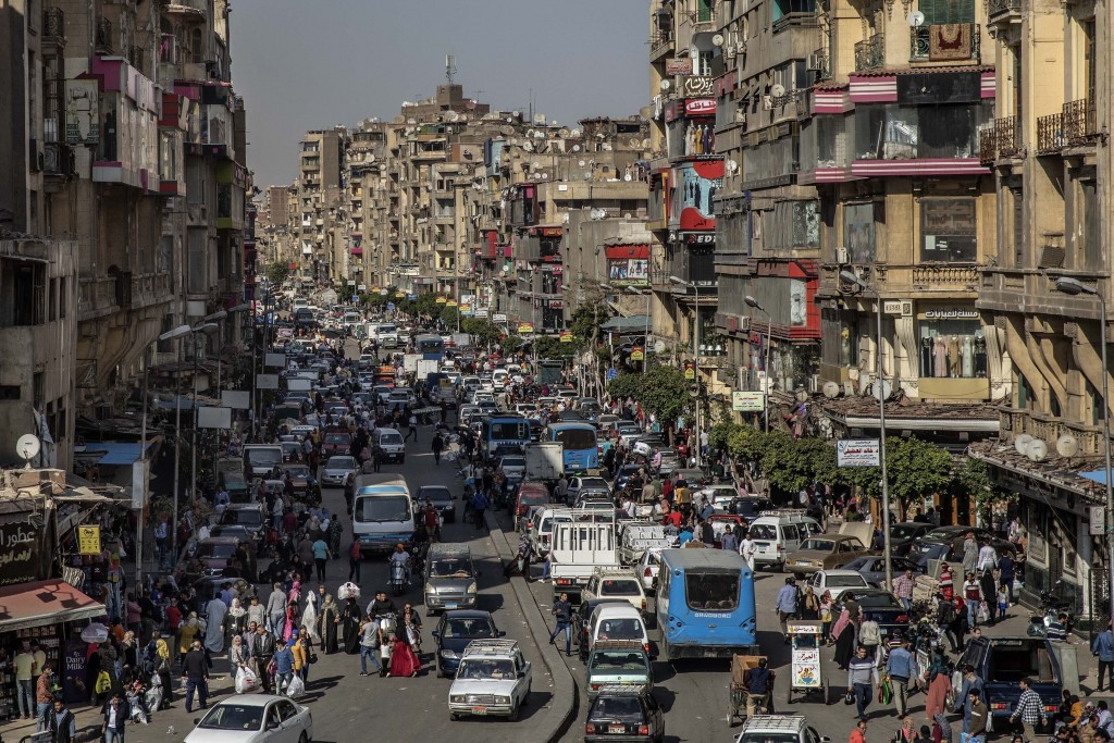 FILE - In this April 14, 2020 file photo, people crowd a street a few hours ahead of curfew in Cairo, Egypt. As Egyptian authorities fight the swellin...