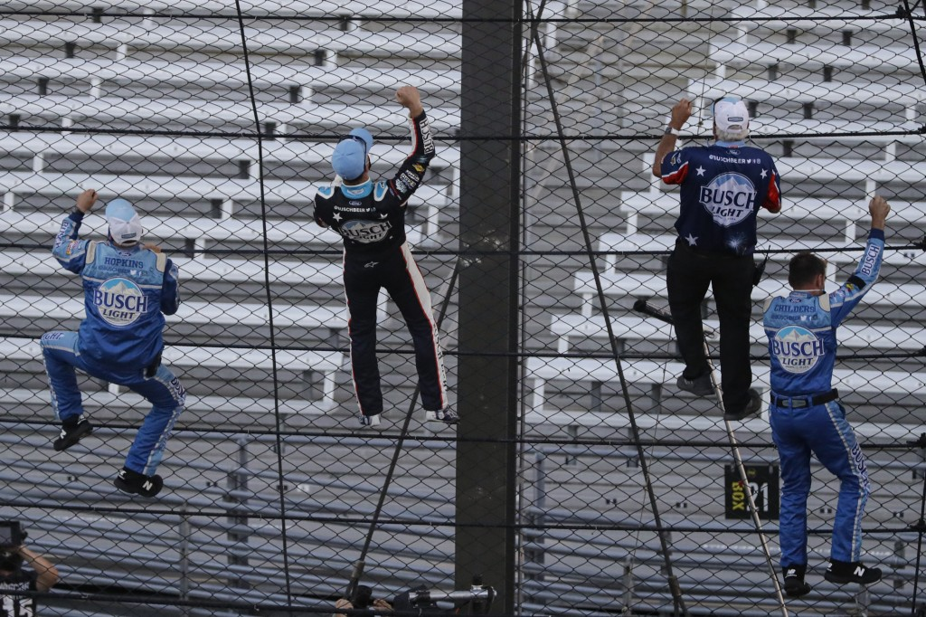 Kevin Harvick, second from left, and some members of the team's crew climb the fence after Harvick won the NASCAR Cup Series auto race at Indianapolis...