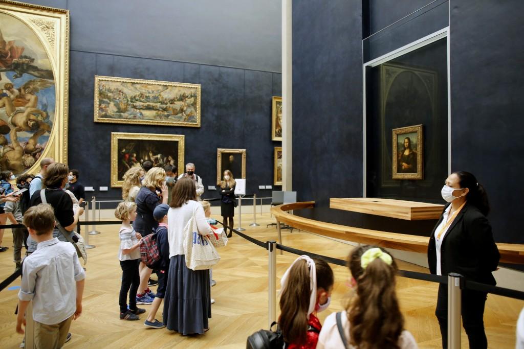 Visitors watch the Leonardo da Vinci's painting Mona Lisa, in Paris, Monday, July 6, 2020. The home of the world's most famous portrait, the Louvre Mu...