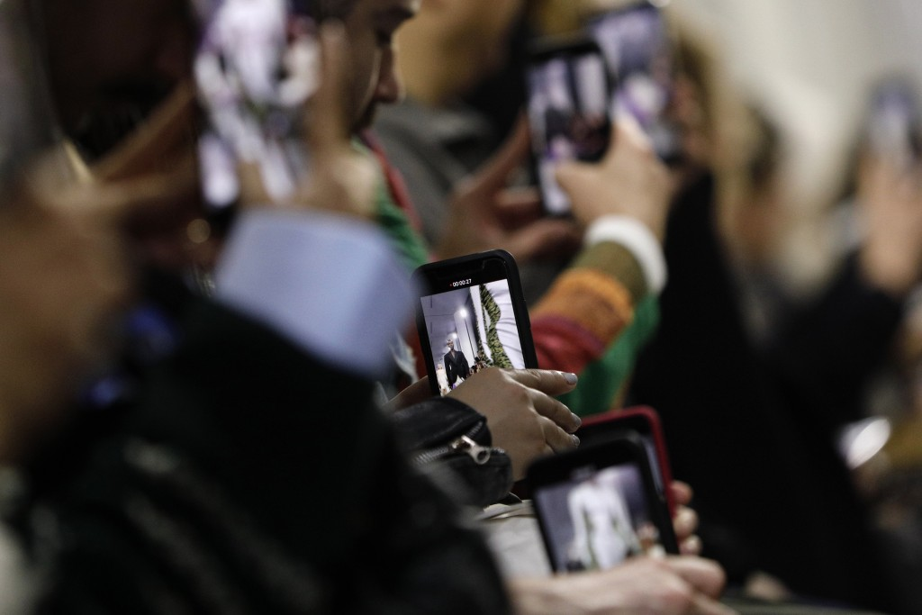 FILE - In this Feb. 27, 2019 file photo, guests use with their cell phones to record the Mugler ready to wear Fall-Winter 2019-2020 collection, that w...