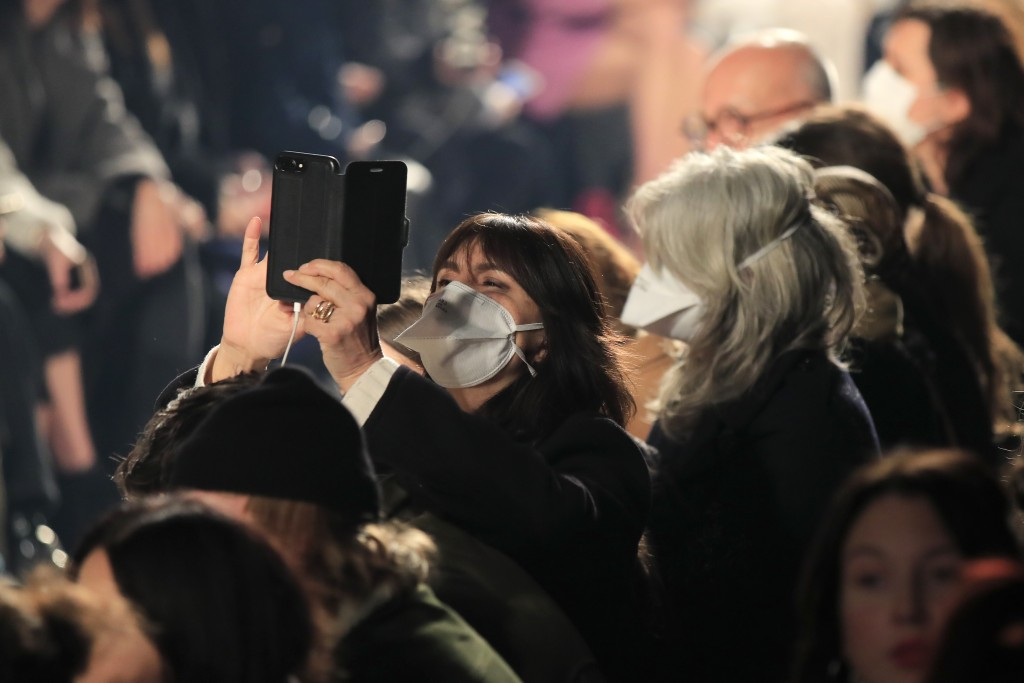 FILE - In this Feb. 27, 2020 file photo, spectators wear protective masks during the Isabel Marant fashion collection during Women's fashion week Fall...