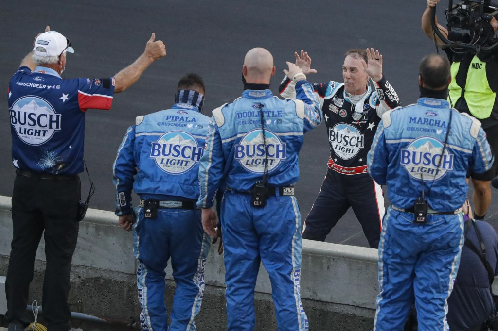 Kevin Harvick, on far side of wall, celebrates with his crew after winning the NASCAR Cup Series auto race at Indianapolis Motor Speedway in Indianapo...