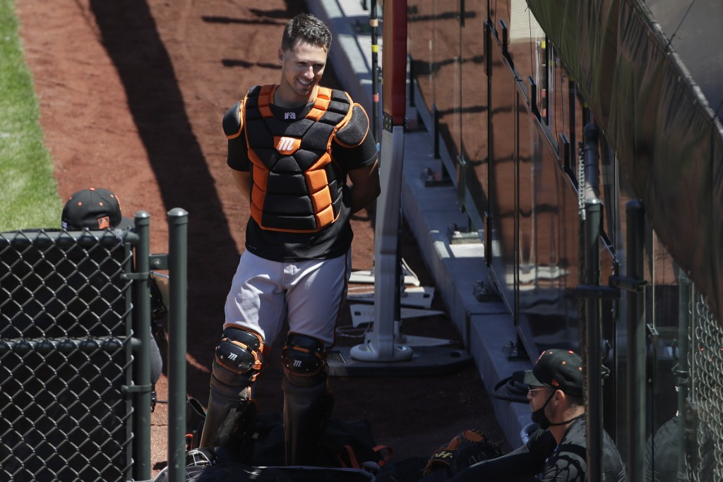 San Francisco Giants catcher Buster Posey, top, talks with manager Gabe Kapler, bottom right, during a baseball practice in San Francisco, Sunday, Jul...