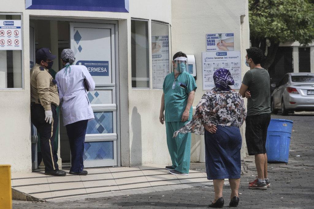 FILE - In this May 11, 2020 file photo, a medical worker wears a mask and face shield at the entrance of the SERMESA hospital in Managua, Nicaragua. W...