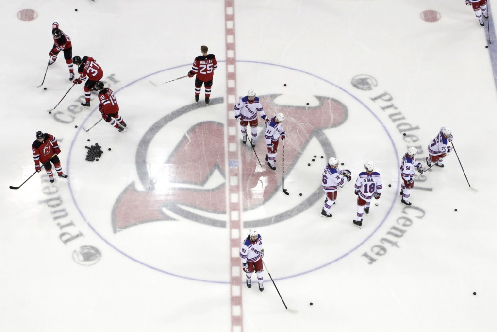 FILE - In this April 1, 2019, file photo, New Jersey Devils, left, and New York Rangers warm up for an NHL hockey game in Newark, N.J. Deputy Commissi...