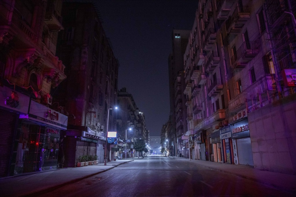 FILE - In this March 29, 2020 file photo, a street is empty during curfew hours due to the coronavirus outbreak, in Cairo, Egypt. Even as Egyptian aut...