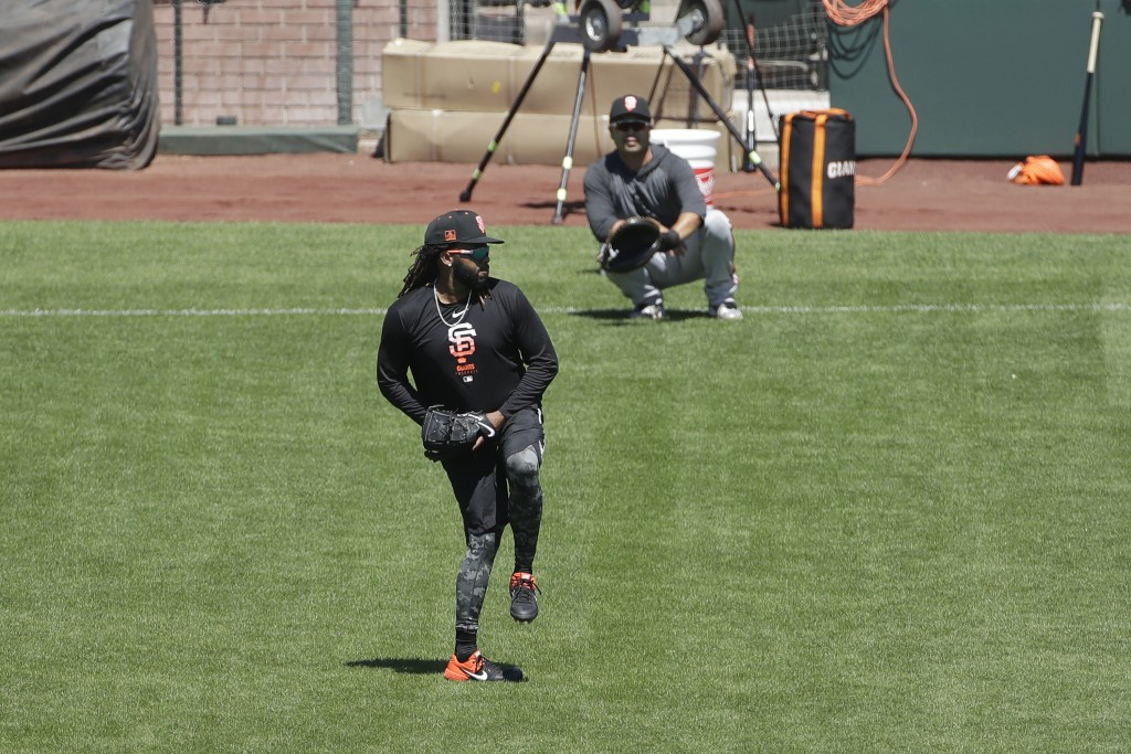 San Francisco Giants pitcher Johnny Cueto, foreground, throws to bullpen catcher Taira Uematsu during a baseball practice in San Francisco, Sunday, Ju...