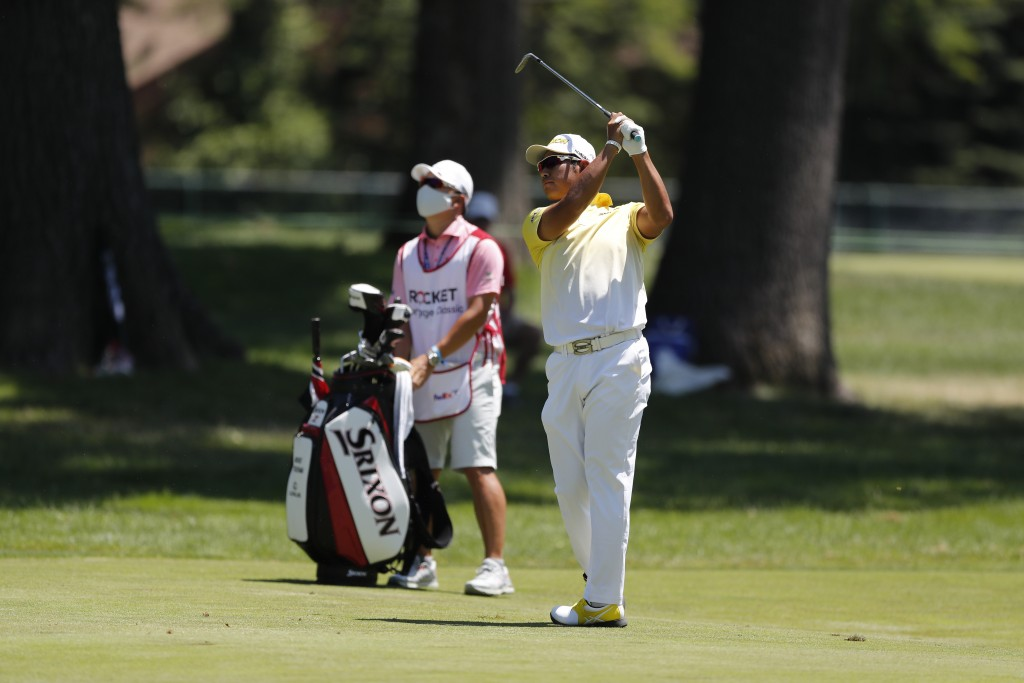 Hideki Matsuyama, right, of Japan, hits from the first fairway during the final round of the Rocket Mortgage Classic golf tournament, Sunday, July 5, ...