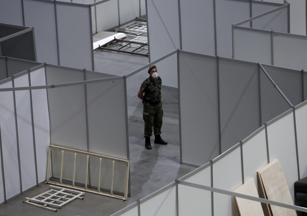 A Serbian soldier walks between treatment areas set up for possible COVID-19  infected patients inside of the Belgrade Arena, in Belgrade, Serbia, Mon...