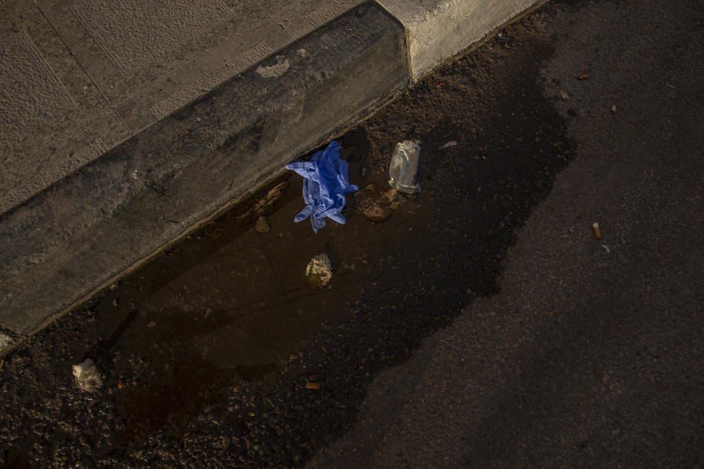 FILE - This April 3, 2020 file photo, shows used medical gloves thrown on a street in Cairo, Egypt. Coronavirus infections are surging in the country ...