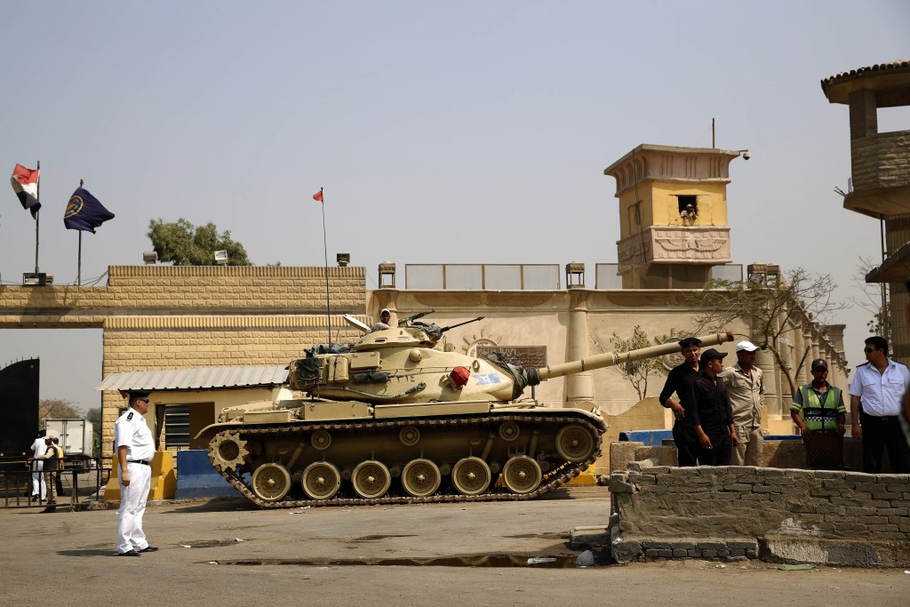 FILE - In this Aug. 2, 2015 file photo, Egyptian security forces stand guard outside one of the entrances of Tora prison, in Cairo, Egypt. Since the c...