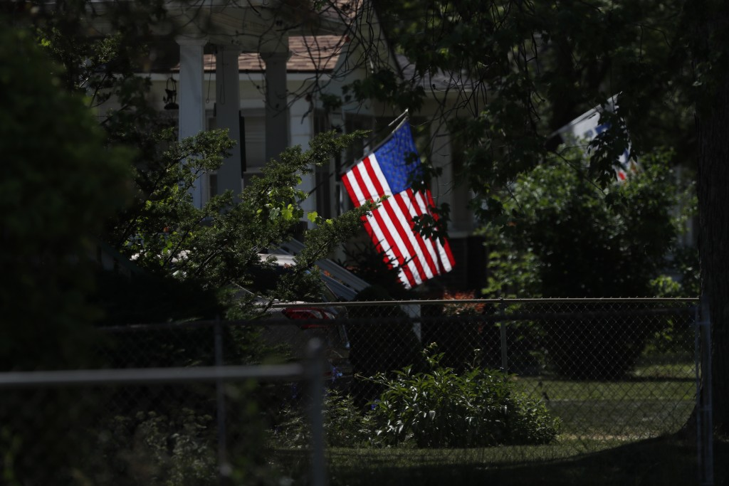 A U.S. flag is lit by the midmorning sun on a neighborhood street in Saginaw, Mich., on Monday, June 29, 2020. President Donald Trump won Saginaw coun...