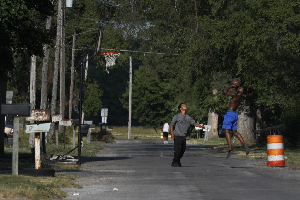 Youths play a game of one-on-one basketball Monday, June 29, 2020, on a neighborhood street on the impoverished east side of Saginaw, Mich. Saginaw ha...