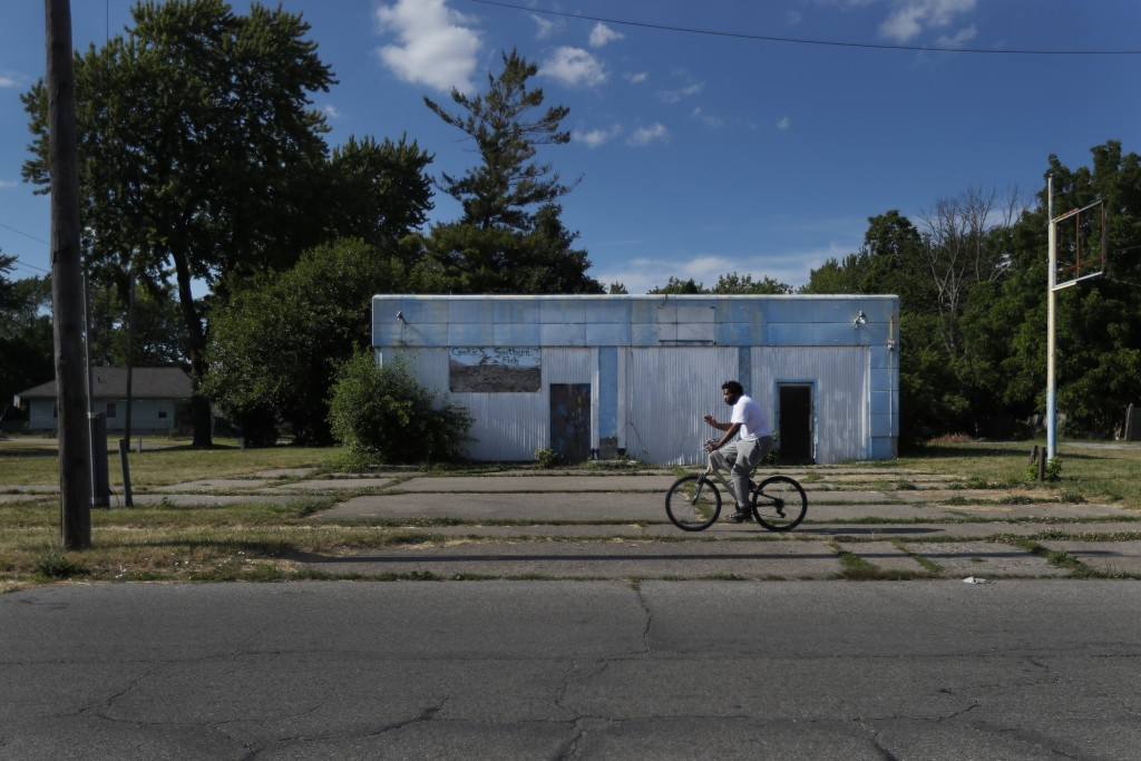 A man rides his bicycle past an abandoned service station in the impoverished east side neighborhood of Saginaw, Mich., on Monday, June 29, 2020. It's...