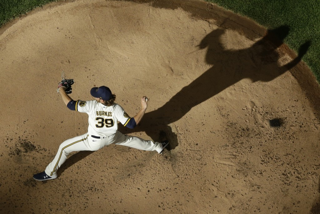 Milwaukee Brewers' Corbin Burnes throws during a practice session Monday, July 6, 2020, at Miller Park in Milwaukee. (AP Photo/Morry Gash)